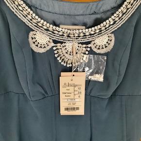 Smuk foret silkekjole med fine detaljer. Kjolen sidder til ved barm og ned til talje hvorfra stoffet er skåret i baner, der giver masser af smuk bevægelse i silken. Kjolen er 115 cm lang og måler 79 cm under bryster, 94 cm over brystet og 79 i taljen.  Kjolen har en lang lynlås i siden.