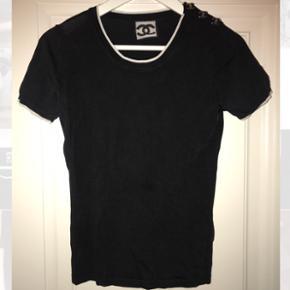Vintage Chanel t-shirt i perfekt stand, med knapper på venstre skulder, som kan åbnes og med hvide kanter. Materiale: 70% viskose og 30% silke Mp: 5500  Str: 38 (kan også passes af en 36)