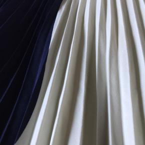 Fin plisseret nederdel fra H&M, i hvid og navy. Lidt slid i kanten, som man ikke ser ved brug. Længde cirka 82 cm. Der er underskørt, så den ikke er gennemsigtig