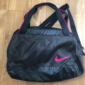 Lækker to dels rum sportstaske fra Nike. Sort med pink detaljer og foer. Brugt få gange - er som ny.