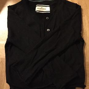 Fin sort cardigan i glatstrikket merinould (fnugger ikke). Klassisk sort cardigan med fine detaljer med små lommer foran og lille slids i siden.