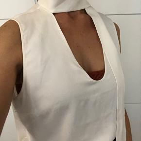 Hvid ærmeløs top i silke med bånd ved kraven. Brugt få gange, men en smule misfarvet i nakke og i armgabene - ikke tydeligt på afstand. Florlet og let gennemsigtig i 100% silke. Rimelig lang og kan derfor let styles ned i nederdele eller bukser
