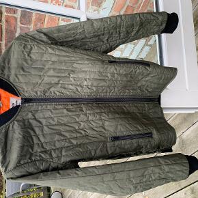 Den klassiske Mads Nørgaard-jakke i fed grøn med orange foer, str. 14 år. Brugt, men ingen huller, pletter eller andet. Vasket i svanemærket, ingen tørretumbling eller røg.