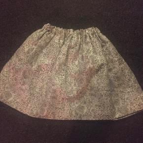 Kort struttende nederdel fra Samsøe Samsøe med sølvfarvet glitter. Der står ikke en størrelse i, men den er lille til mig - som er en 38. Vil mene at den passer en 34 eller evt en lidt lille 36. Købt på et luksus genbrugsmarked, har ingen tegn på slid.
