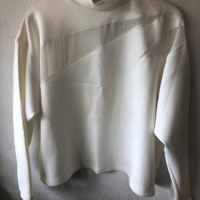 Fed bluse med høj krave  Transparente stykker stof foran og bag.  Super flot