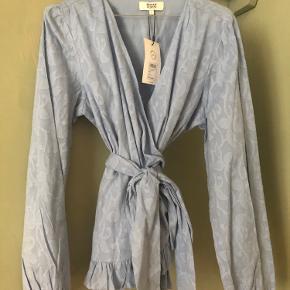 Wrap bluse fra Magasin. StrL - normal i størrelsen. Aldrig brugt, stadig med prismærke.  Prisen er sat udfra hvad jeg vil mene er fair ift stand og nypris, men kom gerne med bud 😊