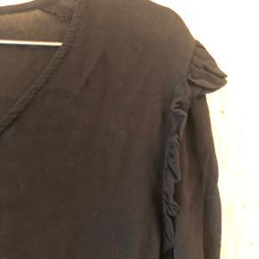 Smuk tunika med flæse detaljer ved skulderen.  Lange ærmer med perle deltaljer.   I en crepe kvalitet.