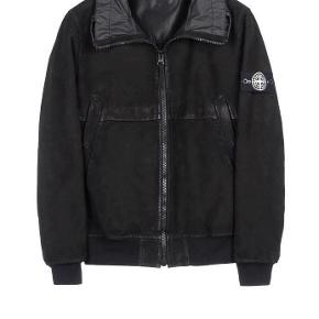 Varetype: Stone Island Tech Waxed SuedeFarve: Sort Oprindelig købspris: 10000 kr. Kvittering haves.  You know the deal. Killer Jacket.  STONE ISLAND TECH WAXED SUEDE  AUTUMN_WINTER ' 012-' 013 Condition 8/10 Jacket in Tech Waxed Suede, fine suede made technical by laminating with an inner polyester mesh. The garment is then all over hand waxed. Snap-fastening diagonal pockets. Yoke with flap on the front. Stretch jersey bottom hem and cuffs. Nylon foldaway hood in raised collar. Zip fly.  Missing inside the inner pocket button.