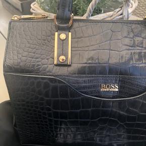 Smuk sort lædertaske fra HUGO BOSS. Den er så god som ny. Meget rummelig. Kan bruges som arbejdstaske mm. Købt i Illum i København. Original pose medfølger.
