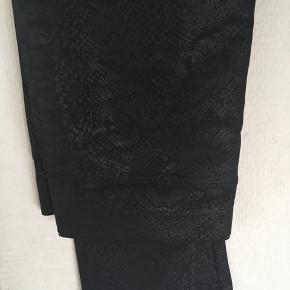 Dejlig leggings i sort med slangeskindsmønster🌸 De har aldrig været brugt og er kun taget ud af emballagen for at tage billede. De er lagt tilbage i emballagen🌸 Det er glatte leggings og har en skinnende effekt🌸 88% polyester 12% elasthane Str. L/XL