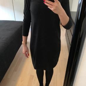 Fin sort kjole med guld lynlås bag på ryggen.