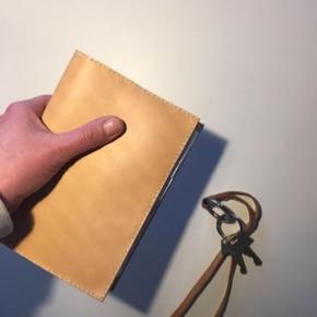 Kernelæder cover til kalender str. Mayland. I stedet kan der indsættes en notesbog, og så har du en fed dagbog eller en travelers notebook.  Enkelt, stilrent, håndlavet og nordisk.  Det fremstilles i hånden og laves ved bestilling.  Hvis du har ønske om bestemte mål, så skriv endelig.  De kan laves med orange, sorte eller lyse syninger.  Laves i kernelæder, i enten sort eller natur.  Læder er et natur materiale, hvor ikke to stykker er ens og alt er håndlavet, derfor kan de variere i udtryk.  Pris 475kr uden kalender/ bog  Kan afhentes i Aalborg, eller sendes med DAO.