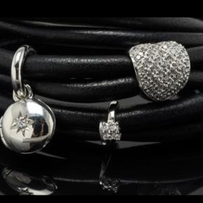 Story by Krantz & Ziegler  Armbånd er af sort lammeskind med charm af sterling sølv, prydet med cubic zirkonia.   Længde 55½ cm.   Nyt og ubrugt