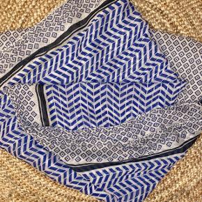 Blå og hvid mønsteret tørklæde af 100 bomuld fra Beck Söndergaard. Tørklædet er ca. 175 cm langt og ca. 100 cm bredt