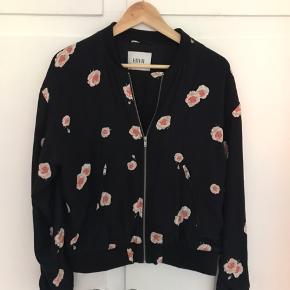 Sort viskose jakke med lyserøde roser. Elastisk rib ved ærmer og talje. Størrelsen er ikke opgivet, men den svarer til Large.