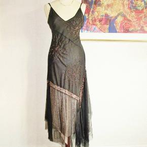 Flot asymetrisk, lang kjole med tyl, chiffon, blonde osv. Regulerbare bh-stropper. Foret som er nudefarvet er 100 % viscose.   Brystvidde: 44 cm x 2 Livvidde: 41 cm x 2 Hoftevidde: max 59 cm x 2 Længde: 125-150 cm    Ingen byt, og prisen er fast