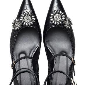 """Varetype: Heels Farve: Sort Oprindelig købspris: 1500 kr.  Sælger de smukke sko/stiletter med lille kitten heel og påsatte """"blomster"""" i sten fra Erdem x H&M samarbejdet. De har en høj hælkappe og 3 spænder hver. Sælges inkl. original (vildt flot) æske, og original skopose.   Er brugt meget lidt, og dette kan kun ses på bunden/sålen af skoen. Ellers som ny."""