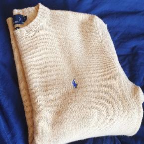 Luksus strik fra Ralph Lauren Trøjen er strikket af det eksklusive merino uld(90%) og Angora uld (rabbit hair 10%)  Farven er en lys gul, tenderende til beige, med et navyblåt broderi på brystet.