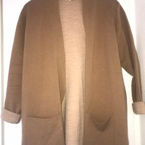 Cardigan er en blanding af brun og beige. Den har en afslappet pasform med lange ærmer. Cardiganen er uden lukning.