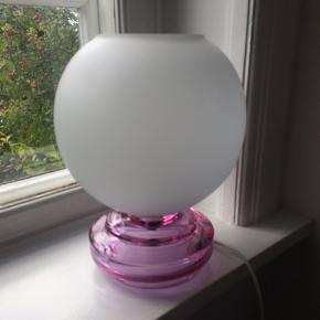 Smuk bordlampe i Art Deco stil med mundblæst glas fod i flot, lys pink farve med kuppel i matteret glas. Fin stand, minimale brugsspor, giver et flot lys.Mål: H31cm/Dia21cm... pris +porto(DAO)... gerne mobilpay eller TS-handel +5%. (Sælger en magen til med blå fod, se anden annonce)
