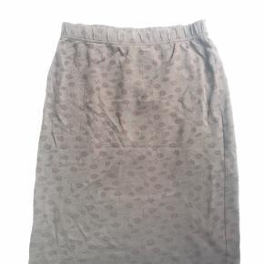 Brun nederdel med blomstret mønster og elastik i taljen. Er pæn uden over bukser også.
