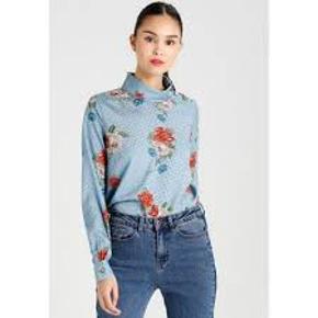 Lyseblå bluse i blomstret print med krave og knap detalje ved venstre skulder.  100% Polyester  Må vaskes ved 30º  Har også bukserne til salg, men de er str. 38.  Brugt 1 eller 2 gange.