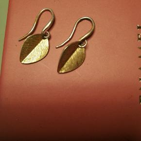 Øreringe fra Pilgrim som forestiller små blade. Med enkelte brugsspor. Bladene måler 1,4 i længden.