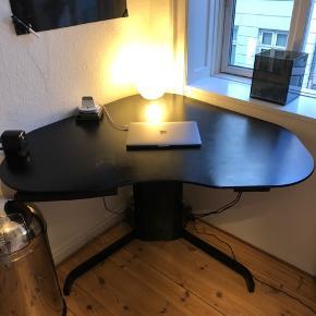 Jeg sælger dette skrive(hæve/sænke)bord grundet flytning.  Den er oprindeligt egetræsfarvet, men er spraymalet sort. Så ønskes træfarver igen, kan det let slibes af.   Den er let at betjene med knapperne og nem at flytte rundt på. Den indeholder opbevaring til skriveredskaber, tape mv., som er skjulet under bordet.   Jeg har selv været rigtig glad for den, da den er super praktisk, flot og rummelig.  Kan kontaktes på 53 37 27 20 eller over appen her for en hurtig handel 1200kr  Kan afhentes på Lille Fredensgade 8,1, 2200 KBH N