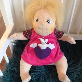 Ida er en skøn, blød og håndlavet dukke fra Rubens Barn med et sødt og dejligt ansigt. De broderede øjne giver Ida et livagtigt og personligt udseende, så Ida vil blive leget med som almindelige dukker, men hun vil helt sikkert også erstatte både sovedyr, krammedyr og mange andre tøjdyr.  Ida er ca. 40 cm lang, vejer ca. 0,8 kg, og hendes siddehøjde er ca. 30 cm.   Alder: 0 år  Rubens Barn Lille Ida kan maskinvaskes og tørretumbles - følg anvisningerne på dukken.  Idas tøj skal vaskes i hånden.  Købspris 499,-
