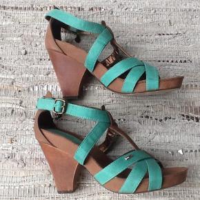 Varetype: Sandaler / Heels Farve: Grøn + brun Oprindelig købspris: 950 kr.  Super smukke sandaler fra Tommy Hilfiger. Skind udvendig og indvendig undtagen sål og hæl.  Rigtig god pasform og behagelige at gå i pga plateau under forfoden. De er 11 cm høje : selve hælen 9 cm og 2 cm plateau i hele skoen længde. Indvendig længde : 25,5 cm. Bredde hvor de er bredest ved forfoden : 8,5 cm. Brugt en enkelt aften.