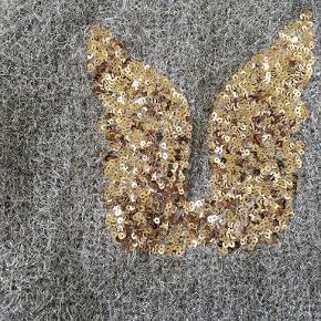 Sjov cardigan i guld med glimmer på ryg og ærmer.  Materialet er polyester og acryl. Stort set ikke brugt.  Størrelsen er S/M.