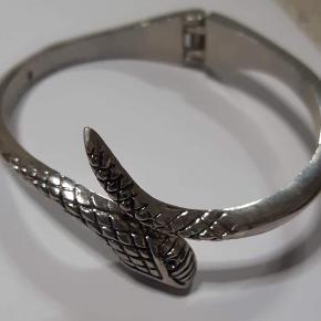 Armbåndet åbnes mellem slangens hoved og hale.