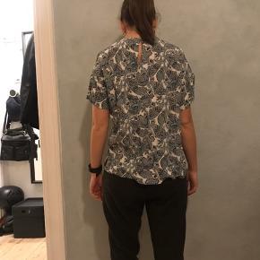 Jeg sælger denne t shirt fra H&M, str. 34.  Der er et hul ved armen, som kan laves.   Nypris 129kr