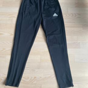 Bukser fra Adidas som aldrig er brugt:) Der er lynlås i siden og lommer med lynlås. Størrelsen passer til en S/M, og længden er 98 cm (foran midtpå). De kan også spændes ind eller ud i maven:)