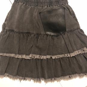 Blød denim nederdel med læderlomme bagpå og elastik i taljen.