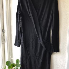 Sort kjole i stræk med elegant snit. Perfekt til arbejde.