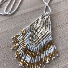 Meget smuk halskæde fra Bali. Aldrig brugt. Kan reguleres i længden. Hvid og guld.