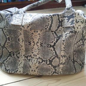 """Smuk """"slangeskinds"""" taske fra det bæredygtige danske mærke Luxalicious.  Den har været brugt nogle gang hvilket ikke kan ses.  Den er gjort i læder med et (som førnævnt) slangeskindslook. Der er en udvendig og en indvendig lynlåslomme  Mål oplyses til interesserede købere, men der kan snildt være en 13' bærbar i den.  Købsprisen var 1800kr  Køber betaler porto"""