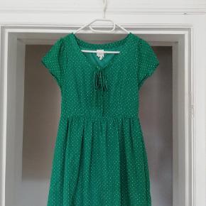 Flot grøn kjole med hvide prikker. Brugt en enkelt gang. Fejler intet. Bindebånd ved kraven. Byd gerne 😊 (jeg sender også gerne flere billeder)
