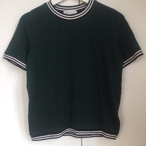 Fin flaskegrøn neo noir T-shirt med sorte og hvidstribede kanter.