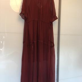 """Meget smuk transparent kjole over size lang kjole fra """" Baum und Pferdgarten"""" Kjole har guldknapper på skuldrene, kort ærme. Under kjole med tynd stropper følger med.  Langt: 146 cm. Materiale :  100 % viskose  Farve red dahlia ( Bordeaux ) Aldrig blevet brugt.  Np: 2199kr   Sender med Dao 37kr Kan afhente på Amager. Bytte ikke! 👗👗"""