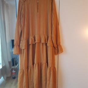 Rigtig smuk kjole i str L . Købt til en fest men da jeg valgte en anden kjole, blev den desværre aldrig brugt. Fremgår derfor nærmest som nu. Kan afhentes på Amager eller sendes på købers regning. Efter aftale kan vi også.mødes i København. Farve gylden  Kom evt med bud
