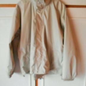 REGNJAKKE Farve: Lys grå  Flot ny kvalitets jakke, 100% vandtæt og vindtæt  Overvidde 140cm. Længde 78 cm. Er foret så god til kolde dage Hætte med snøre, der gemmes i kraven  2 sidelommer med lynlås 1 inderlommer  Lynlåslukning + overfald med velcrolukning og trykknapper Velcro ved håndled så vidden kan reguleres Snøre elastik nederst på jakken til regulering af vidden. 100% polyester Bytter ikke Sender med DAO uden omdeling, fremme på 2-4 dage Ts pay eller mobilpay