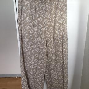 Super cool vintage culotte bukser med god vidde og etisk-inspireret print i beige og hvid. De har elastik i taljen, lommer i siden og er ankellange (afhængig af din højde selvfølgelig). 100% viskose. Str L men passer også str M. Kom med et bud.   Varen befinder sig i 9520 Skørping. Sender med DAO.  Se også min øvrige annoncer. Jeg sælger tøj, sko og accessories. Pt er min shop fuld af vintagekup, high street fund og mærkevarer i mange forskellige str. Kig forbi og spøg endelig!