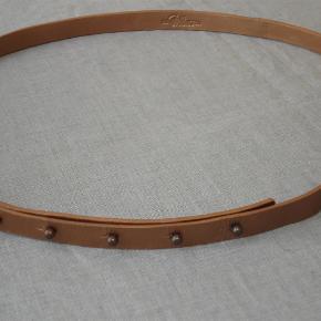 Varetype: Helt smalt bronze-læderbælte. Lukkes uden sædvanligt spænde Størrelse: 90 X 1/5 cm Farve: Bronze Oprindelig købspris: 595 kr.  Superelegant, smalt bronze-læder-bælte fra Benedikte Utzon. 90 cm ved inderste hul - kan bruges til 105 cm. Bredden er bare 1,5 cm. Lukkes med metaldupper, der skal presses ned i tilsvarende huller. Altså intet spænde. Enkelt og elegant. Aldrig brugt. BYTTER IKKE!