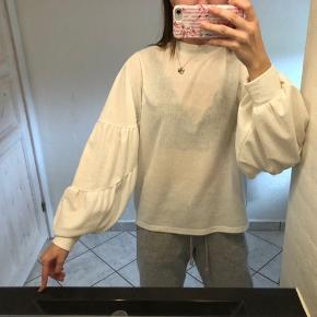 Hvid, gennemsigtig trøje med store ærmer.