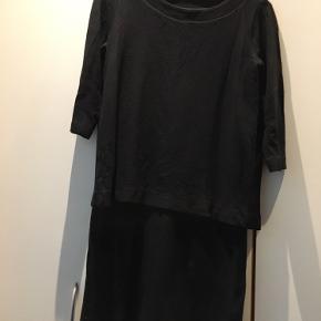 Stram sort kjole, der ligner at den er i to dele.