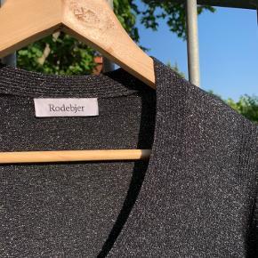Sort, tynd striktrøje fra Rodebjer med slidser i ærmerne. Bemærk at trøjen glimter meget mere end det kan ses på billederne.   Mål: Skulderlængde: 53 cm Længde fra v-hals: 34 cm