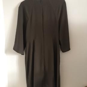 Mørkegrøn kjole med bindeeffekt om livet og tre-kvart lange brede ærmer. Lynlås i ryggen.