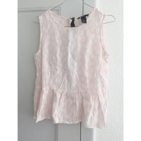 Lyserød og hvid prikket trøje med kontrast farvet lynlås og flæset peplum effekt.  Sender gerne med DAO :)